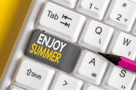 Conceptual hand writing showing Enjoy Summer. Concept meaning taking a break from school and spending holidays in the beach White pc keyboard with note paper above the white background