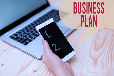 Word writing text Business Plan. Business photo showcasing Structural Strategy Goals and Objectives Financial Projections woman laptop computer smartphone mug office supplies technological devices