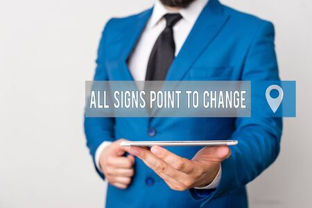 Writing note showing All Signs Point To Change. Business concept for Necessity of doing things differently new vision Businessman in blue suite with a tie holds lap top in hands