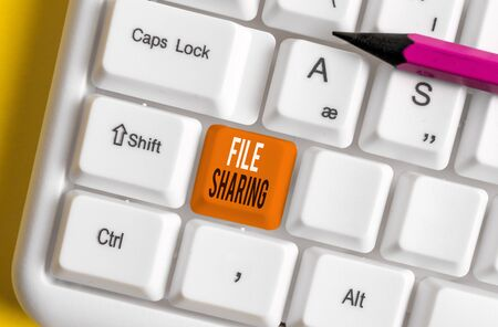 Handwriting text File Sharing. Conceptual photo transmit files from one computer to another over a network White pc keyboard with empty note paper above white background key copy space