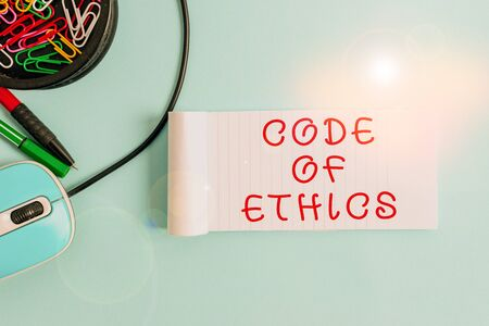 Handwriting text Code Of Ethics. Conceptual photo basic guide for professional conduct and imposes duties Notebook and writing equipment with computer mouse above pastel backdrop