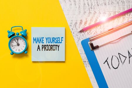 Writing note showing Make Yourself A Priority. Business concept for Think in your own good first demonstratingal development Notepad clipboard colored paper sheet alarm clock wooden background Stock Photo