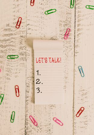 Text sign showing Let S Talk. Business photo showcasing they are suggesting beginning conversation on specific topic Stripped ruled notepad clips lying wooden old retro vintage background