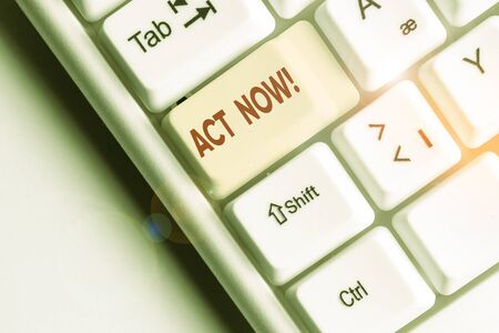 Conceptual hand writing showing Act Now. Concept meaning fulfil the function or serve the purpose of Take action Do something White pc keyboard with note paper above the white background