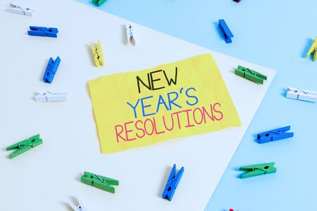 Handwriting text writing New Year S Resolutions. Conceptual photo Wishlist List of things to accomplish or improve Colored clothespin paper empty reminder yellow blue floor background office