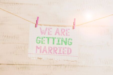 Writing note showing We Are Getting Married. Business concept for Engagement Wedding preparation Loving couple Clothesline clothespin rectangle shaped paper reminder white wood desk Foto de archivo