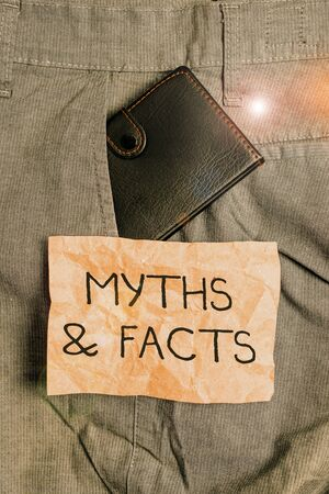 Word writing text Myths And Facts. Business photo showcasing usually traditional story of ostensibly historical events Small little wallet inside man trousers front pocket near notation paper