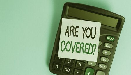 Text sign showing Are You Covered Question. Business photo showcasing asking someone or patient if he have insurance Portable electronic calculator device blank sticky note colored background