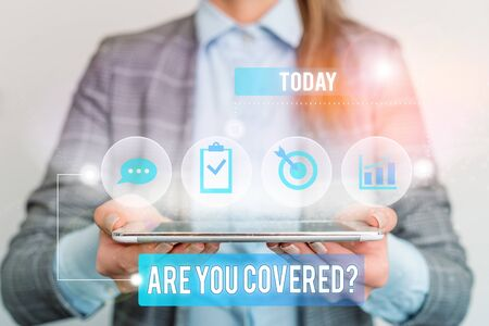 Writing note showing Are You Covered Question. Business concept for asking someone or patient if he have insurance Female human wear formal work suit presenting smart device Zdjęcie Seryjne