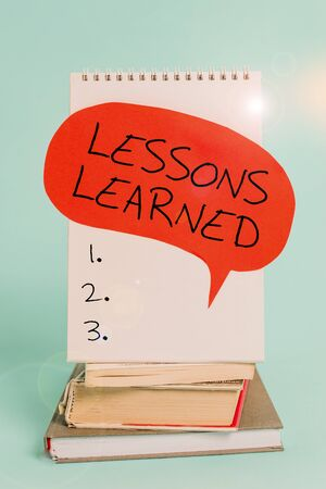 Writing note showing Lessons Learned. Business concept for the knowledge or understanding gained by experience Spiral notebook speech bubble stacked old books cool pastel background Banque d'images