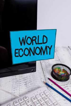Conceptual hand writing showing World Economy. Concept meaning Global Worldwide International markets trade money exchange Note paper taped to black screen near keyboard stationary