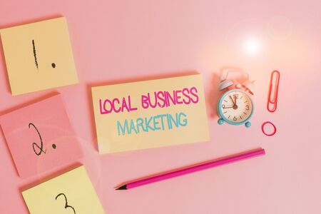 Writing note showing Local Business Marketing. Business concept for Localized specification on Store characteristic Blank notepads marker rubber band alarm clock clip colored background