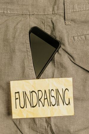 Writing note showing Fundraising. Business concept for act of collecting or producing money for a particular purpose Smartphone device inside trousers front pocket note paper