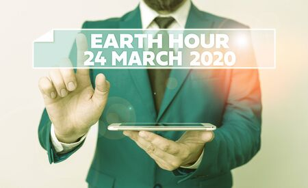 Handwriting text Earth Hour 24 March 2020. Conceptual photo Celebrate Sustainability Save the Planet Lights Off Businessman with pointing finger in front of him
