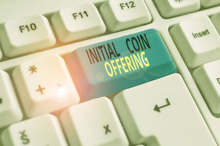 Text sign showing Initial Coin Offering. Business photo showcasing crowdfunding using cryptocurrencies raising capital White pc keyboard with empty note paper above white background key copy space