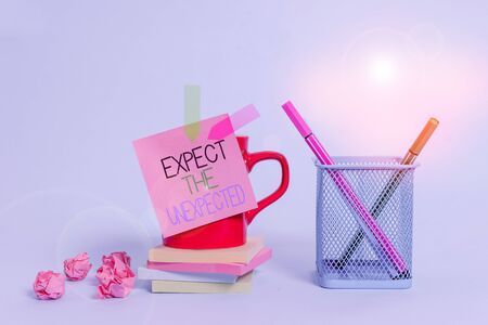 Word writing text Expect The Unexpected. Business photo showcasing Anything can Happen Consider all Possible Events Cup pens holder note banners stacked pads paper balls pastel background