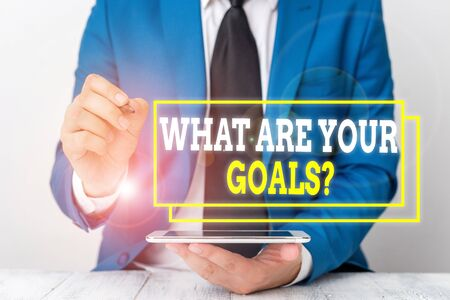 Conceptual hand writing showing What Are Your Goals Question. Concept meaning ask the Desired End Results to know the plans Businessman pointing with pen in empty copy space