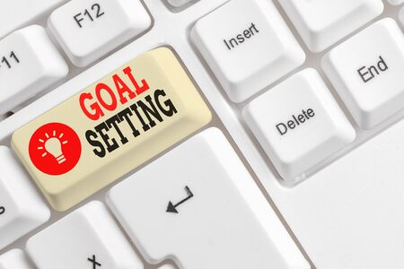 Word writing text Goal Setting. Business photo showcasing process of identifying something that you want to accomplish White pc keyboard with empty note paper above white background key copy space