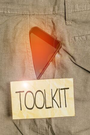 Writing note showing Toolkit. Business concept for set of tools kept in a bag or box and used for a particular purpose Smartphone device inside trousers front pocket note paper