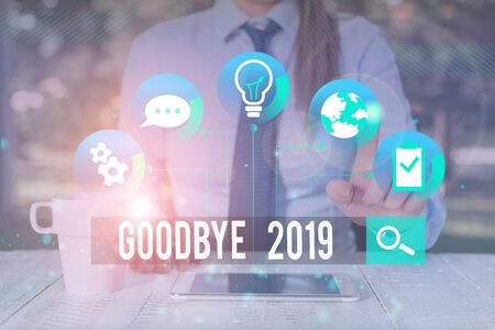Handwriting text writing Goodbye 2019. Conceptual photo expressing good wishes during parting at the end of the year Female human wear formal work suit presenting presentation use smart device