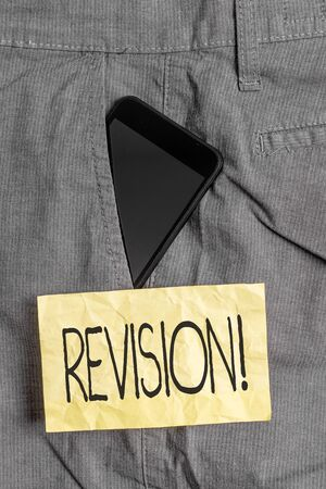Writing note showing Revision. Business concept for action of revising over someone like auditing or accounting Smartphone device inside trousers front pocket note paper 版權商用圖片