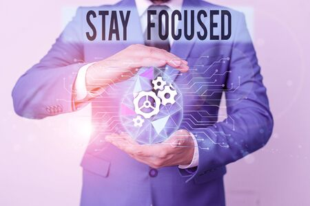 Conceptual hand writing showing Stay Focused. Concept meaning direct time and attention to a limited number of issues Male human wear formal suit presenting using smart device Stok Fotoğraf