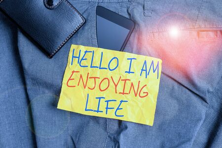 Writing note showing Hello I Am Enjoying Life. Business concept for Happy relaxed lifestyle Enjoy simple things Smartphone device inside trousers front pocket with wallet