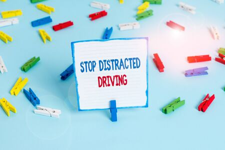 Conceptual hand writing showing Stop Distracted Driving. Concept meaning asking to be careful behind wheel drive slowly Colored clothespin papers empty reminder blue floor officepin