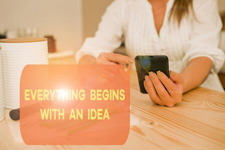 Writing note showing Everything Begins With An Idea. Business concept for steps you take to turn an idea into a reality woman using smartphone and technological devices inside the home
