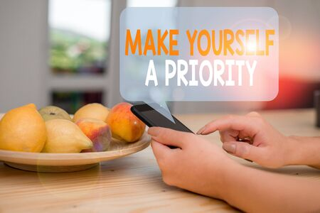 Word writing text Make Yourself A Priority. Business photo showcasing Think in your own good first demonstratingal development woman using smartphone office supplies technological devices inside home