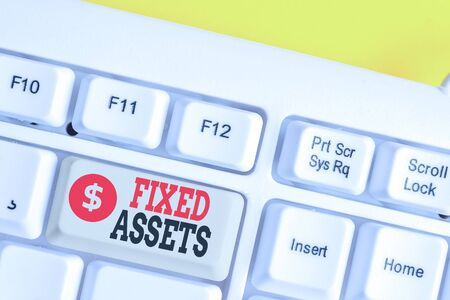 Text sign showing Fixed Assets. Business photo showcasing longterm tangible piece of property or equipment a firm owns White pc keyboard with empty note paper above white background key copy space