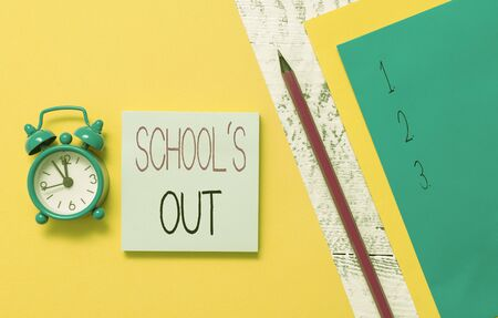 Conceptual hand writing showing School S Is Out. Concept meaning classes are over for the time being End of the school day Notepads marker colored paper sheets alarm clock wooden background
