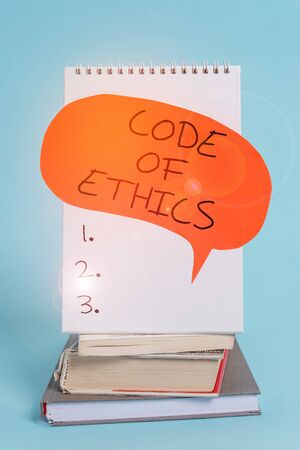 Writing note showing Code Of Ethics. Business concept for basic guide for professional conduct and imposes duties Spiral notebook speech bubble stacked old books cool pastel background Standard-Bild