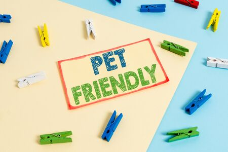 Writing note showing Pet Friendly. Business concept for used to describe a place that is suitable or allowed for pets Colored clothespin paper reminder with yellow blue background 版權商用圖片