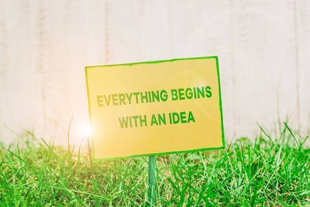 Handwriting text writing Everything Begins With An Idea. Conceptual photo steps you take to turn an idea into a reality Plain empty paper attached to a stick and placed in the green grassy land