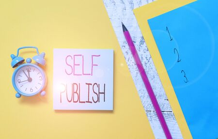 Conceptual hand writing showing Self Publish. Concept meaning published their work independently and at their own expense Notepads marker colored paper sheets alarm clock wooden background Stock fotó