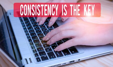 Text sign showing Consistency Is The Key. Business photo text full Dedication to a Task a habit forming process woman laptop computer smartphone mug office supplies technological devices Foto de archivo