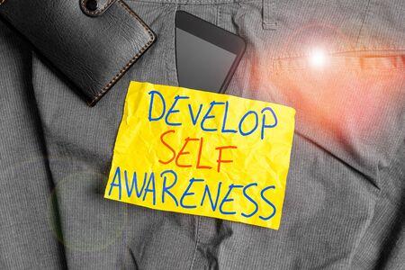 Escribir nota mostrando desarrollar la conciencia de uno mismo. Concepto de negocio para aumentar el conocimiento consciente del carácter propio Dispositivo smartphone dentro del pantalón bolsillo delantero con billetera Foto de archivo