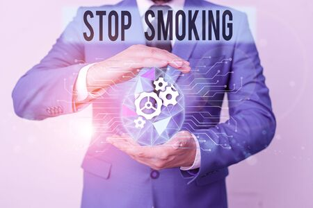 Conceptual hand writing showing Stop Smoking. Concept meaning the process of discontinuing or quitting tobacco smoking Male human wear formal suit presenting using smart device 版權商用圖片