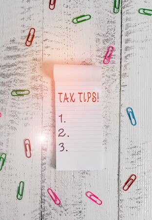 Text sign showing Tax Tips. Business photo showcasing compulsory contribution to state revenue levied by government Stripped ruled notepad clips lying wooden old retro vintage background