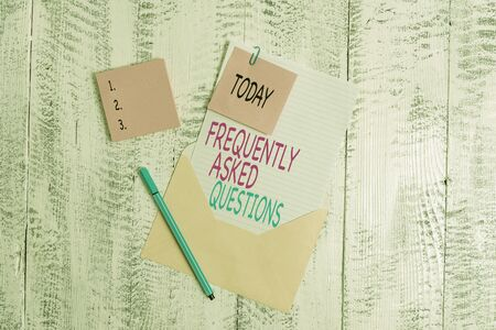Conceptual hand writing showing Frequently Asked Questions. Concept meaning inquries that been informed more than one time Envelope blank sheet sticky note ballpoint wooden background