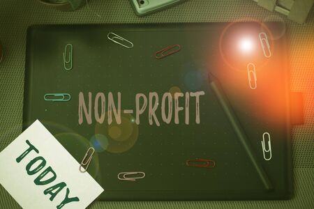 Conceptual hand writing showing Non Profit. Concept meaning type of organization that does not earn profits for its owners Scissors and equipments math book above textured backdrop