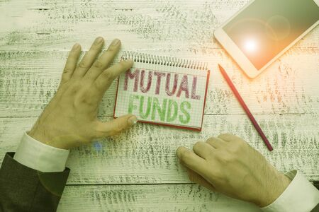 Conceptual hand writing showing Mutual Funds. Concept meaning collection of stocks bonds or other securities from investors Stock Photo