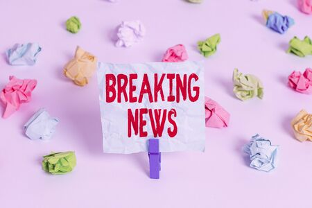 Handwriting text Breaking News. Conceptual photo Special Report Announcement Happening Current Issue Flashnews Colored crumpled papers empty reminder white floor background clothespin Stock Photo