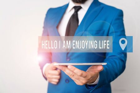 Writing note showing Hello I Am Enjoying Life. Business concept for Happy relaxed lifestyle Enjoy simple things Businessman in blue suite with a tie holds lap top in hands