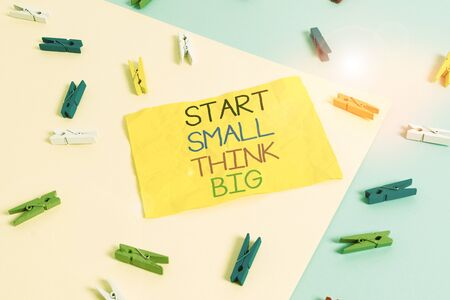 Handwriting text writing Start Small Think Big. Conceptual photo Initiate with few things have something great in mind Colored clothespin paper empty reminder yellow blue floor background office