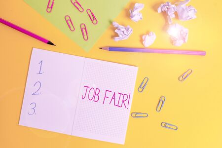 Word writing text Job Fair. Business photo showcasing event where employers offer information about their companies Blank squared notebook pencils paper sheet crushed balls colored background