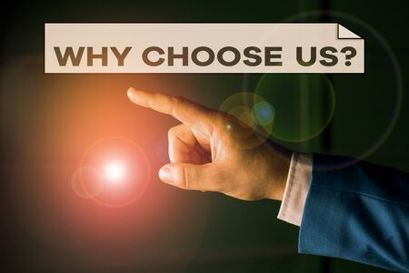 Writing note showing Why Choose Us Question. Business concept for Reasons for choosing our brand over others arguments Isolated hand pointing with finger. Business concept pointing finger