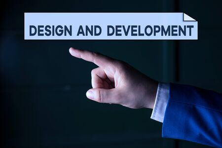 Writing note showing Design And Development. Business concept for Defining the Specification of Products and Services Isolated hand pointing with finger. Business concept pointing finger