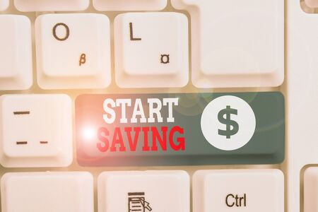 Writing note showing Start Saving. Business concept for money that a demonstrating keeps in an account in a bank or like White pc keyboard with note paper above the white background Stock Photo